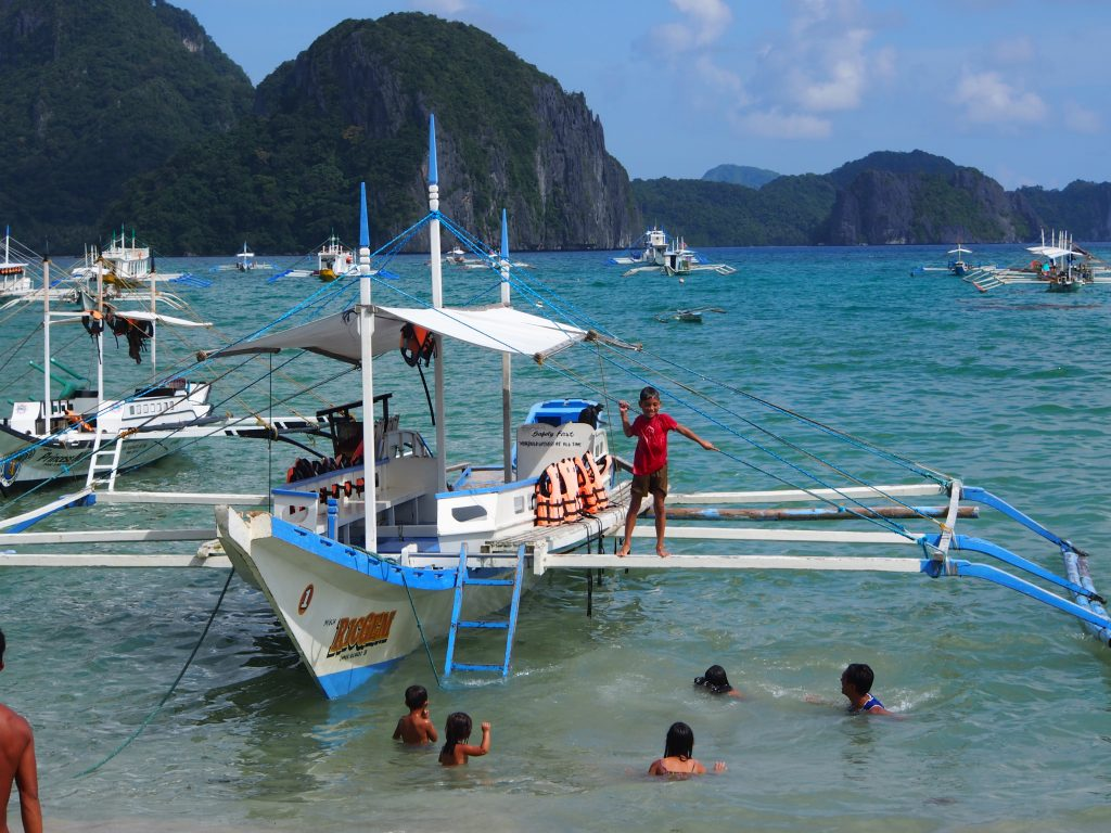 Children swimming from a boat, El Nido, Palawan, Philippines.