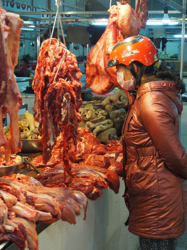 Lady checking out meat in Vietnam