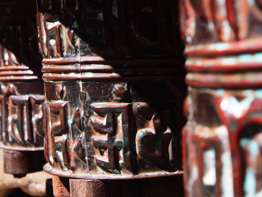 Prayer wheels with raised sanskrit inscriptions