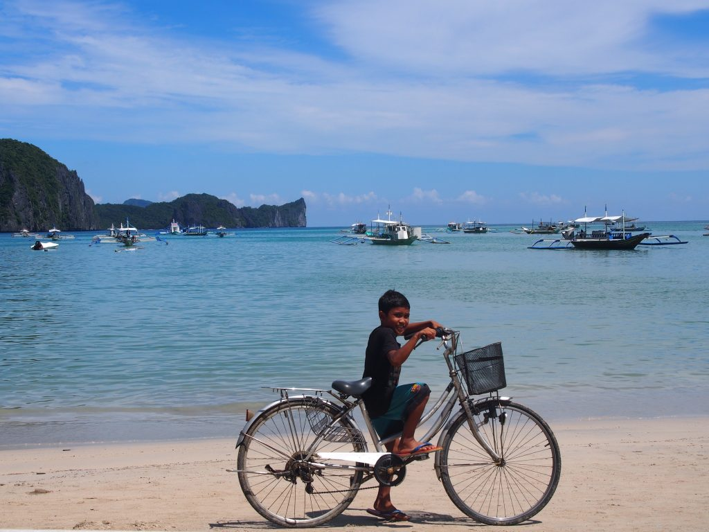 Boy and a bike on the beach,El Nido ,Palawan ,Phillipines ,S.E. Asia