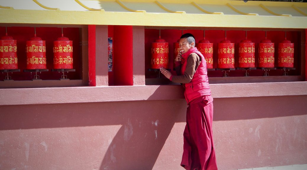 Young Monk in front of prayer wheels on his phone